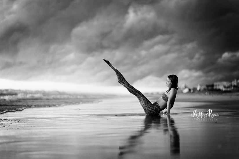 black and white image of mermaid in front of pier on beach with stormy skies