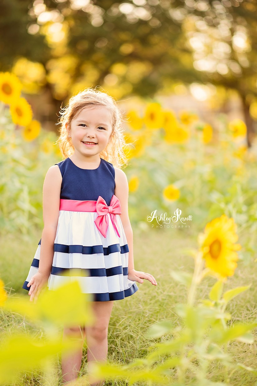 little girl standing in sunflower field