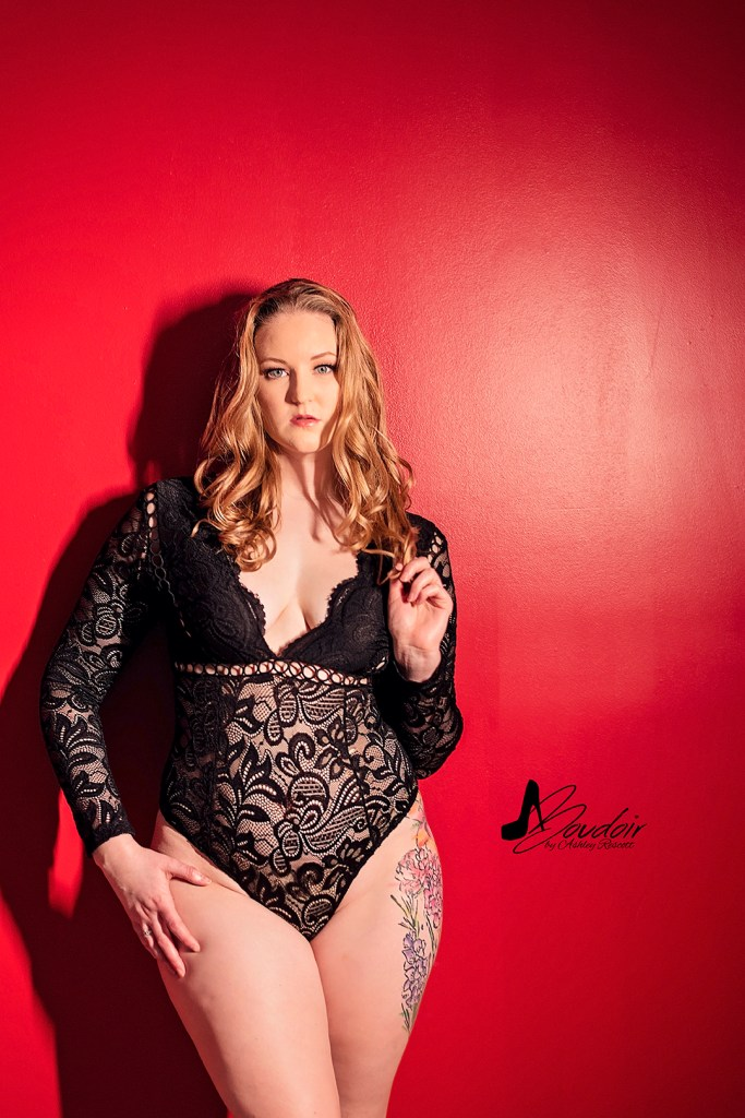 woman standing in front of red wall in black lace bodysuit