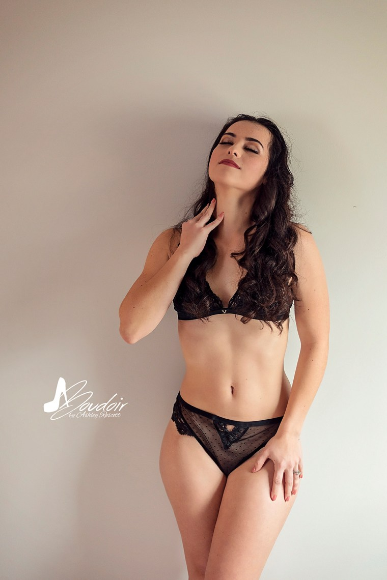 boudoir image of woman standing against wall