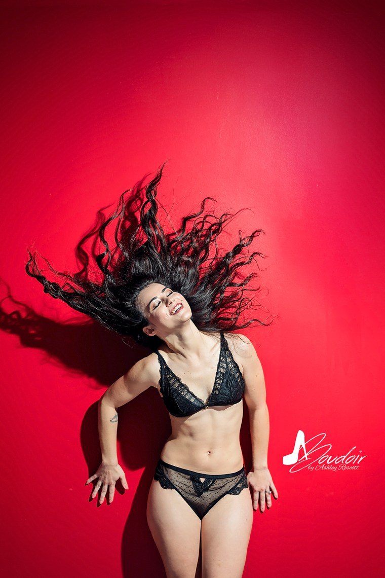 brunette woman in black bra & panties flipping her hair against a red wall