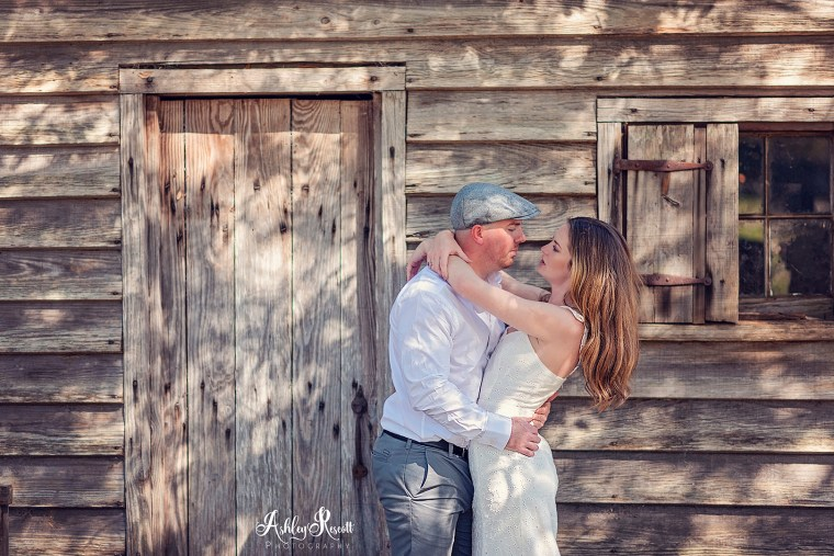 betrothed couple in front of cabin looking at each other