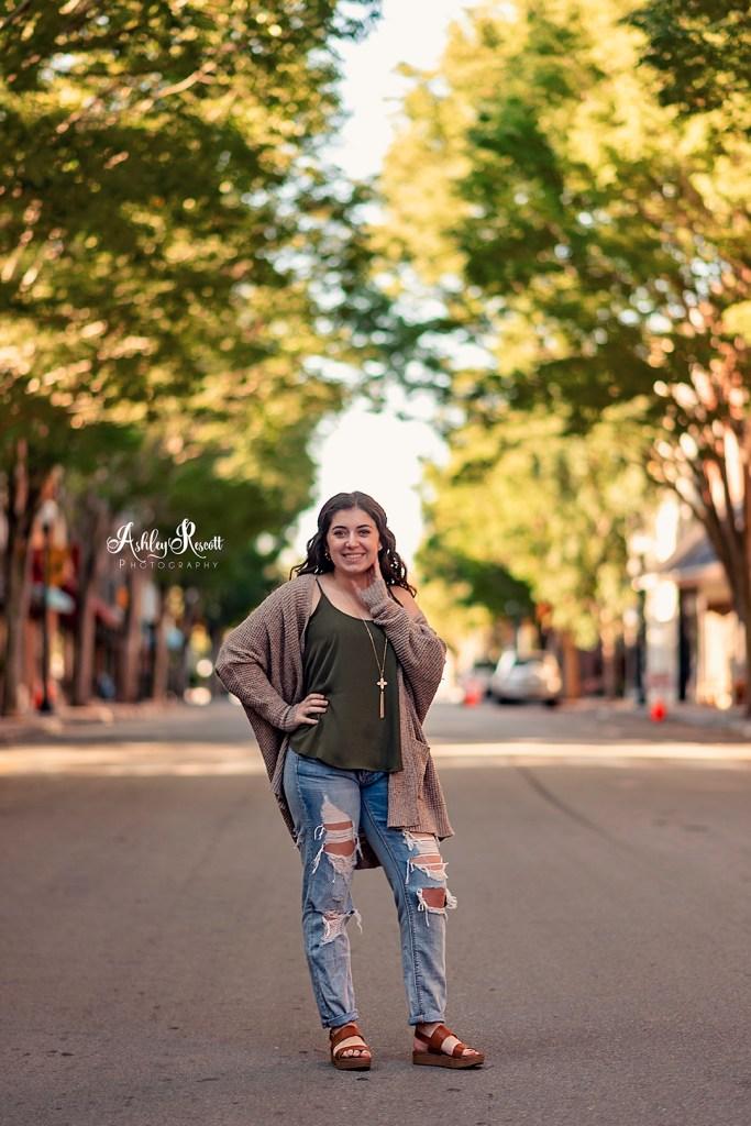 senior girl standing in middle of street