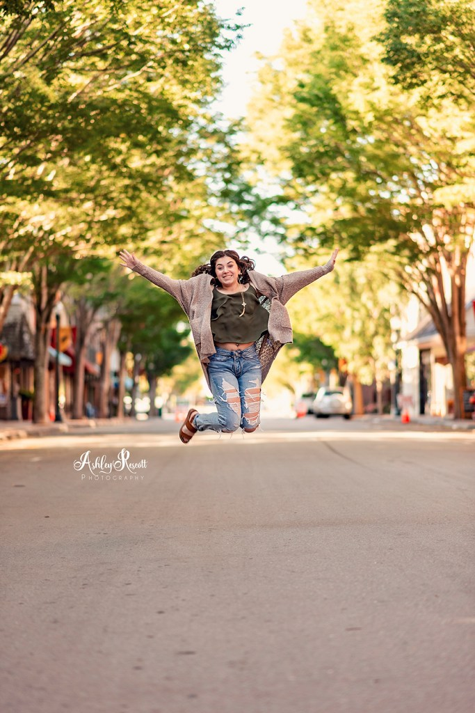 teen girl jumping in middle of street
