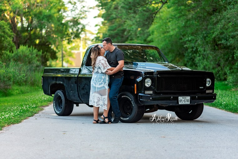 couple kissing in front of pickup truck