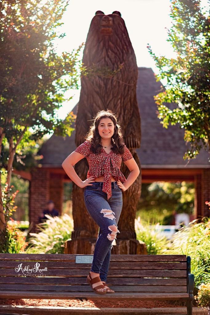 senior girl in front of wooden bear