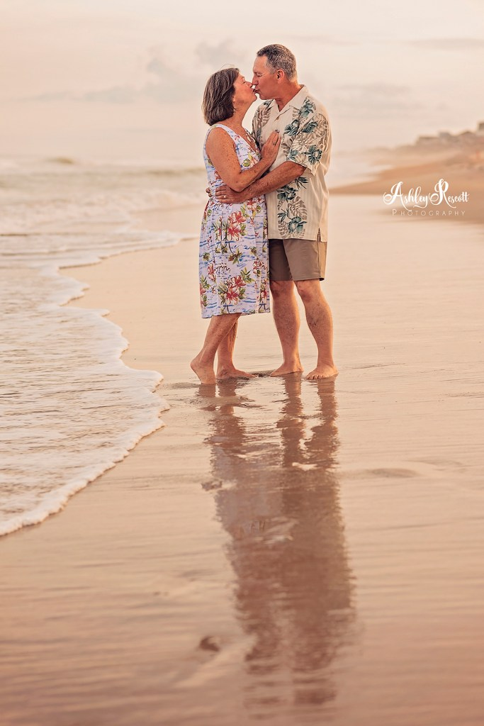 couple standing in water on beach