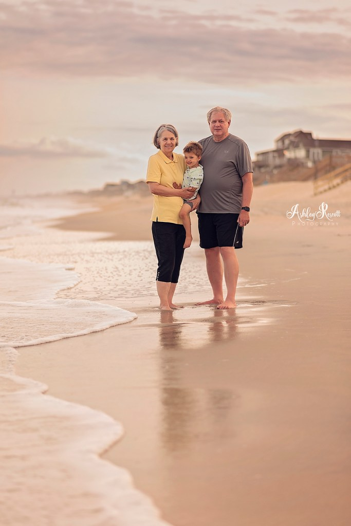 grandparents with grandson on beach