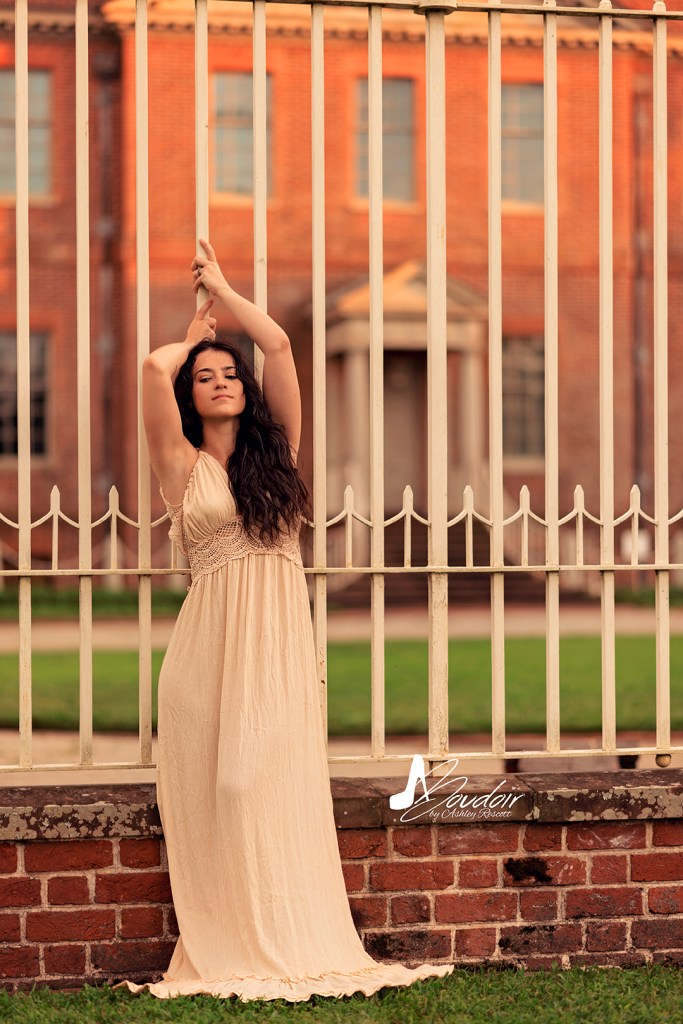 woman standing against fence in front of palace