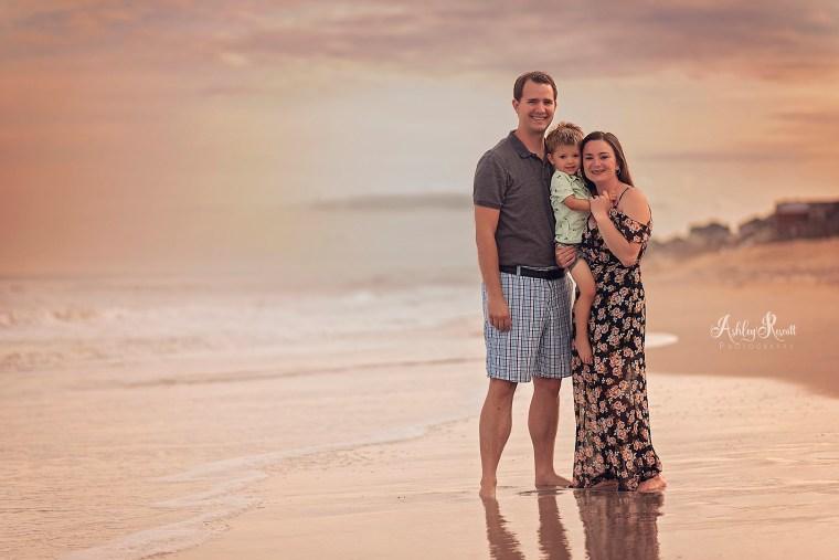parents with son on beach