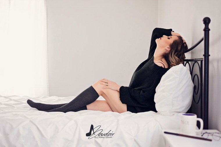 woman lying in bed in sweater and knee socks