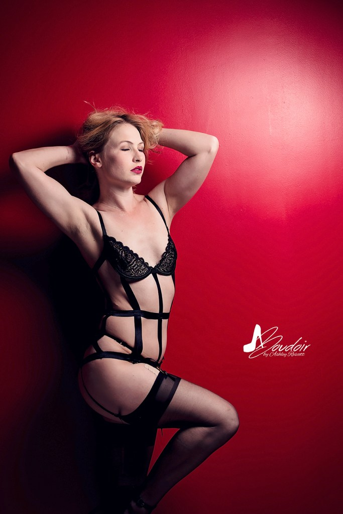 woman leaning against red wall in black strappy lingerie