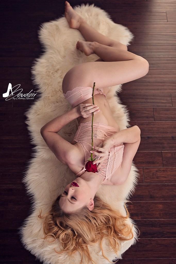 woman lying on sheepskin rug holding a rose