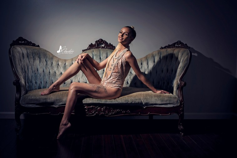 blonde boudoir model on couch with dramatic boudoir lighting