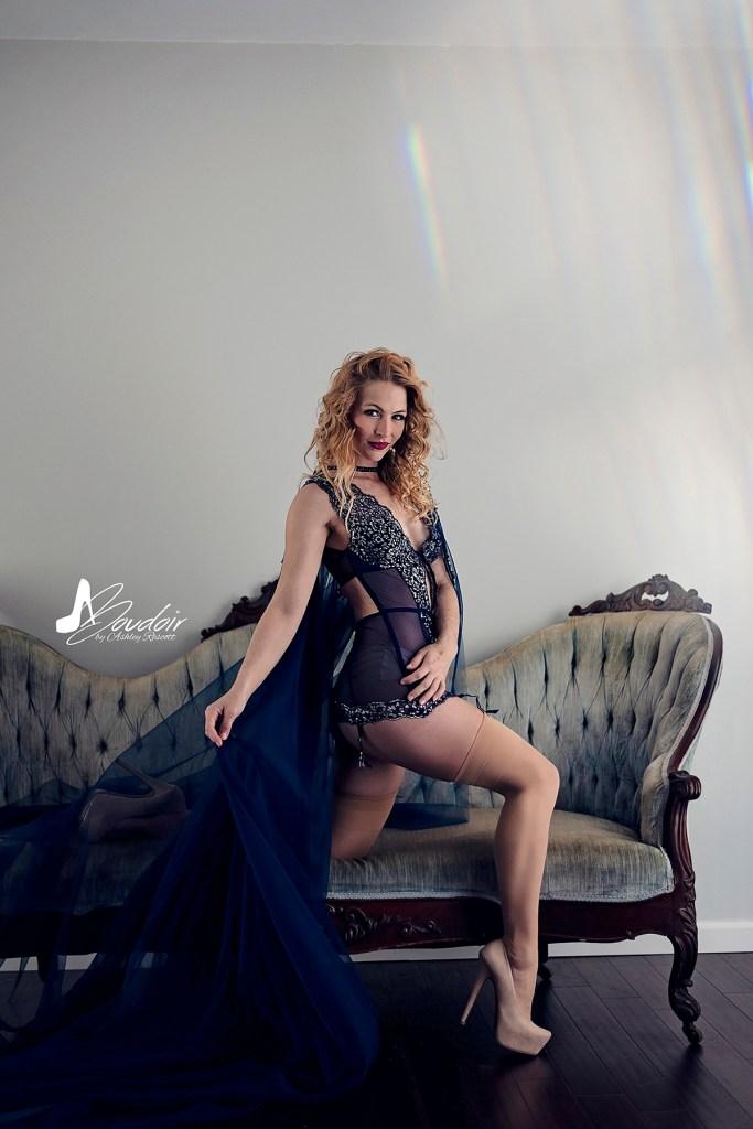 boudoir portrait of blonde model kneeling on couch wearing a blue cape