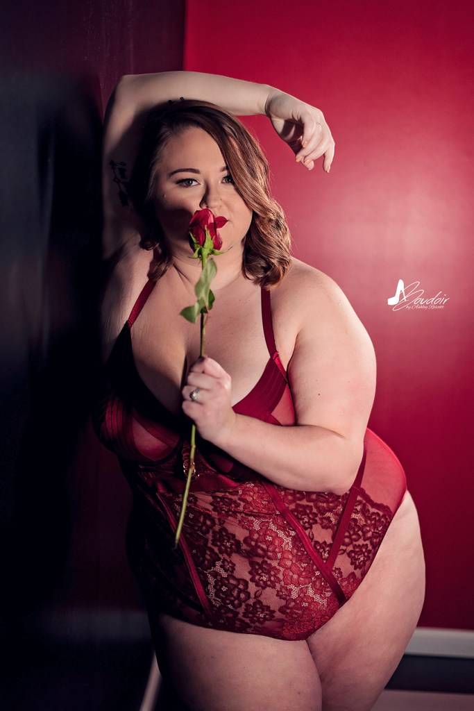 curvy boudoir model in red lingerie smelling rose