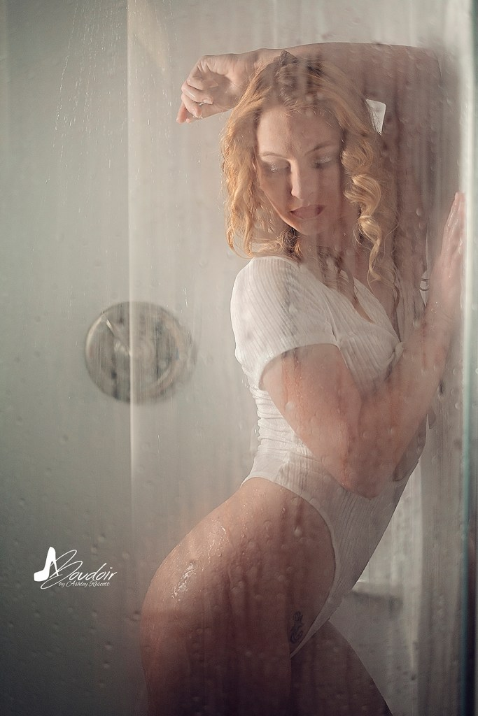 model leaning against shower wall while water comes down, looking down