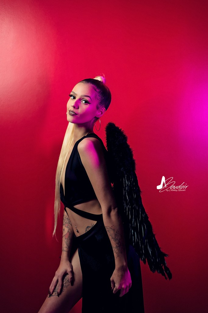 blonde model with dark angel vibes and pink accent light
