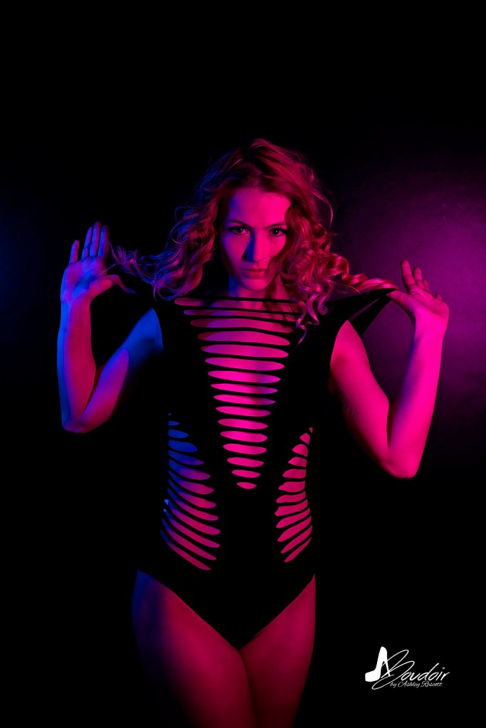 model playing with body suit in neon light