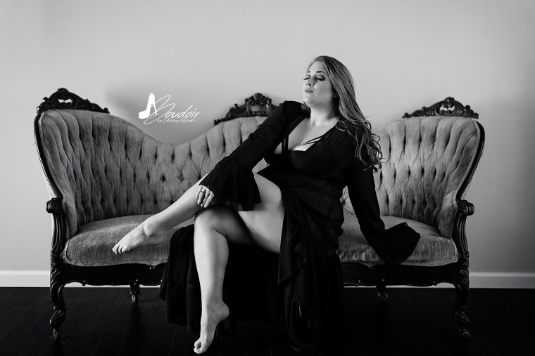 black and white boudoir portrait of woman sitting on couch