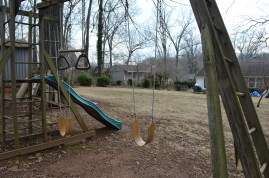 A lonely swing set, longing for warm spring days and children to come play.