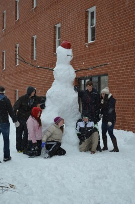 Students getting their picture taken with the snowman they built