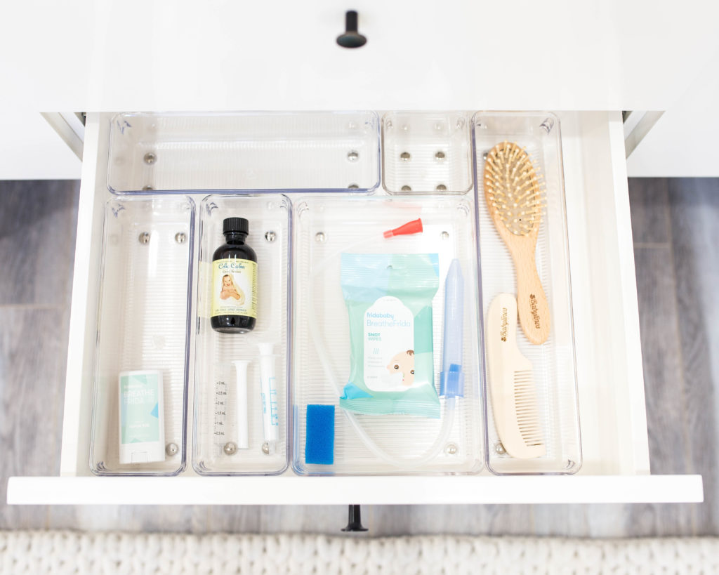 7 Baby Nursery Organization Ideas Every New Mom Should Follow by popular US life and style blogger Ashley Terk: image of a white drawer with Linus Shallow Drawer Organizers and The Container Store Clear Plastic Storage Bins with medicine syringes, medicine, nose wipes, comb and brush in them.