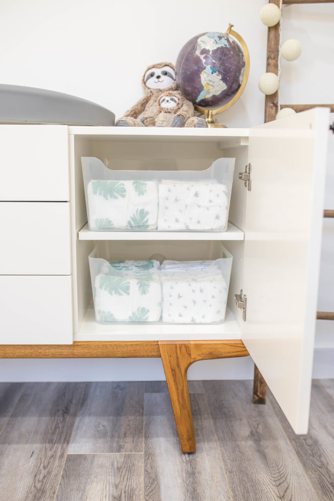 7 Baby Nursery Organization Ideas Every New Mom Should Follow by popular US life and style blogger Ashley Terk: image of a midcentury modern white dresser with a black globe and stuffed sloths resting on top and with clear bins from The Container Store inside storing baby diapers.