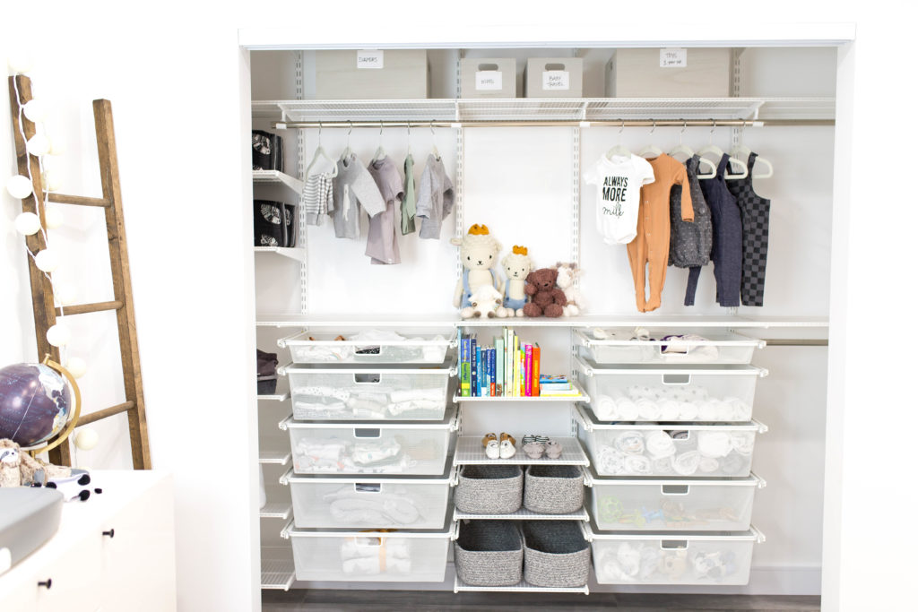 7 Baby Nursery Organization Ideas Every New Mom Should Follow by popular US life and style blogger Ashley Terk: image of a an organized closet by Organization and Relocation with a Custom Elfa Closet Design, bins, and pull out drawers from The Container Store containing baby onesies, jumpers, shirts, and sweaters, stuffed animals, baby moccasins, muslin swaddle blankets and board books.