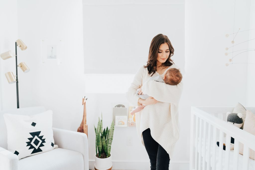 Baby Boy Nursery ideas featured by top Los Angeles life and style blogger, Ashley Hodges: mom looking lovingly at her baby boy stood in his nursery, next to a white armchair and white baby crib