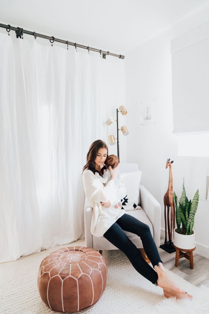 Baby Boy Nursery ideas featured by top Los Angeles life and style blogger, Ashley Hodges: mom sat on a white armchair holding her baby boy in his nursery