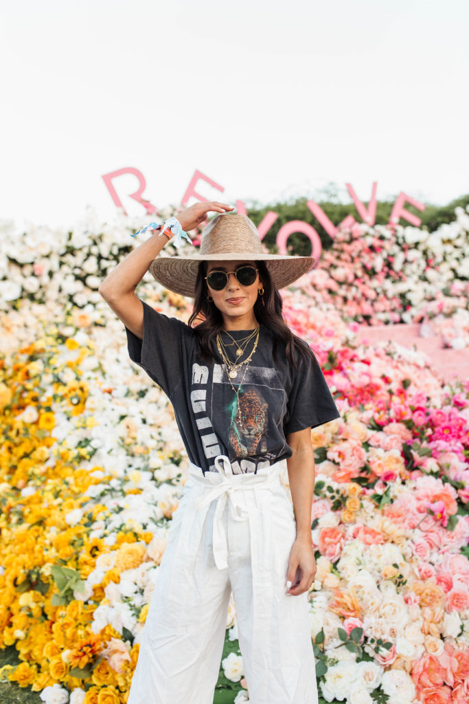 Revolve Festival Looks featured by top US fashion blogger Ashley Hodges; Image of a woman wearing black tee and white pants.