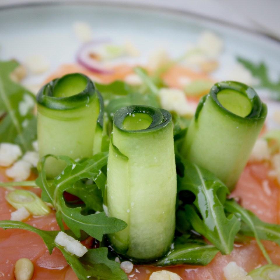 Zalmcarpaccio met komkommer, rucola en pijnboompitten
