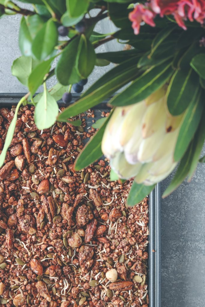 Overhead photo of choccie crunch granola on a baking tray in the background, with native leaves and a protea flower in the foreground
