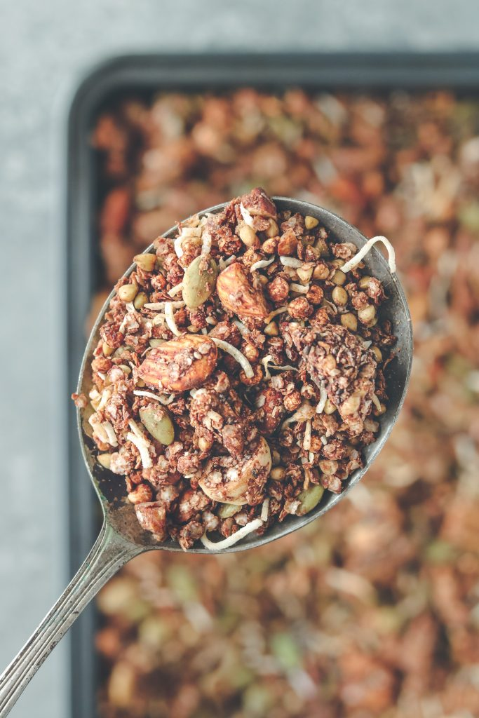 Close-up overhead photo of choccie crunch granola on a large serving spoon in focus, and a baking tray filled with granola blurred out in the background.