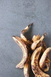 Overhead shot of overripe banana skins against a grey concrete tabletop