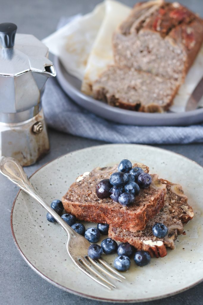 Front-on photo of two slices of banana bread served on a plate with fresh blueberries in the foreground, and a coffee perculator and banana bread loaf sitting in the background