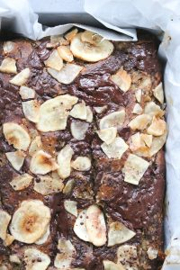 Overhead close-up shot of banana bread in the baking tin. This variation has dark chocolate and banana chips on top.