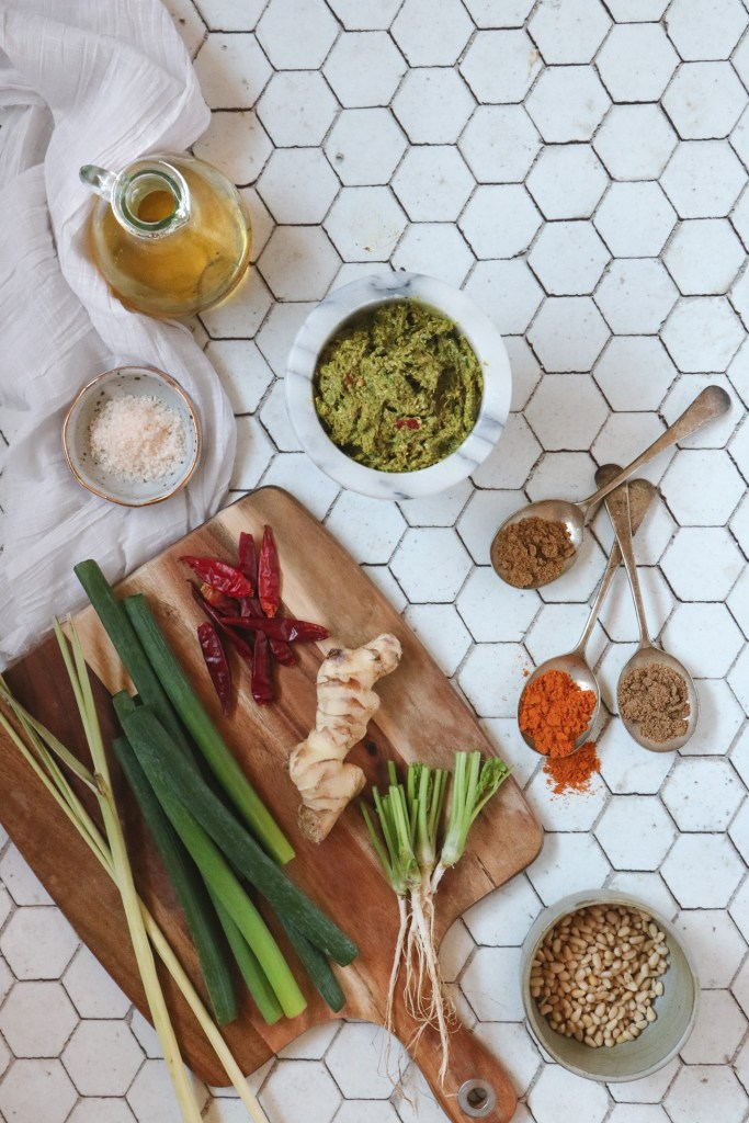Overhead shot of ingredients used for low FODMAP laksa paste on a white hexagonal tiled table