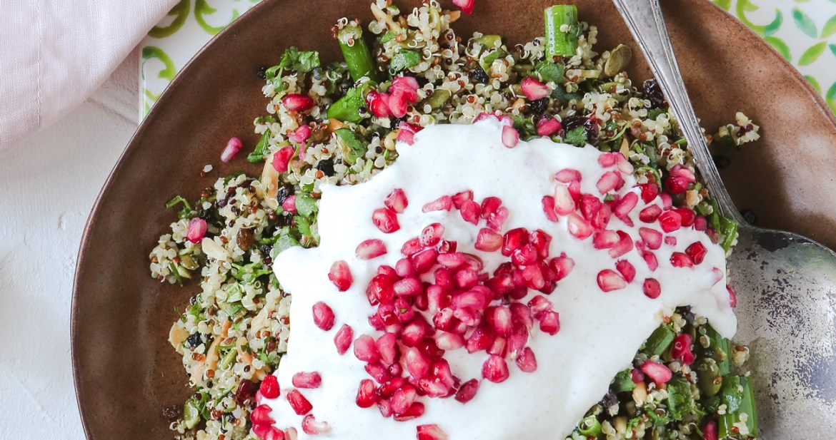 Overhead shot of Cypriot grain salad in a rust coloured serving bowl, topped with yoghurt and pomegranate seeds. Styled with a lime and aqua ceramic tile and soft pink napkin