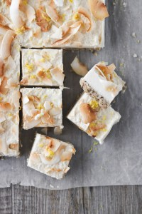 Close-up, overhead photo of lemon and macadamia slice, topped with lemon zest and toasted coconut flakes. Some squares have been cut and one is on its side, showing the cream and biscuit layers