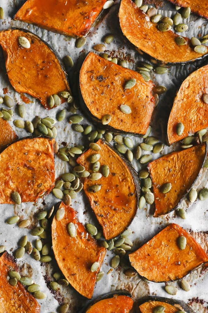 Overhead shot of maple roasted pumpkin with pepitas on a baking tray, fresh out of the oven