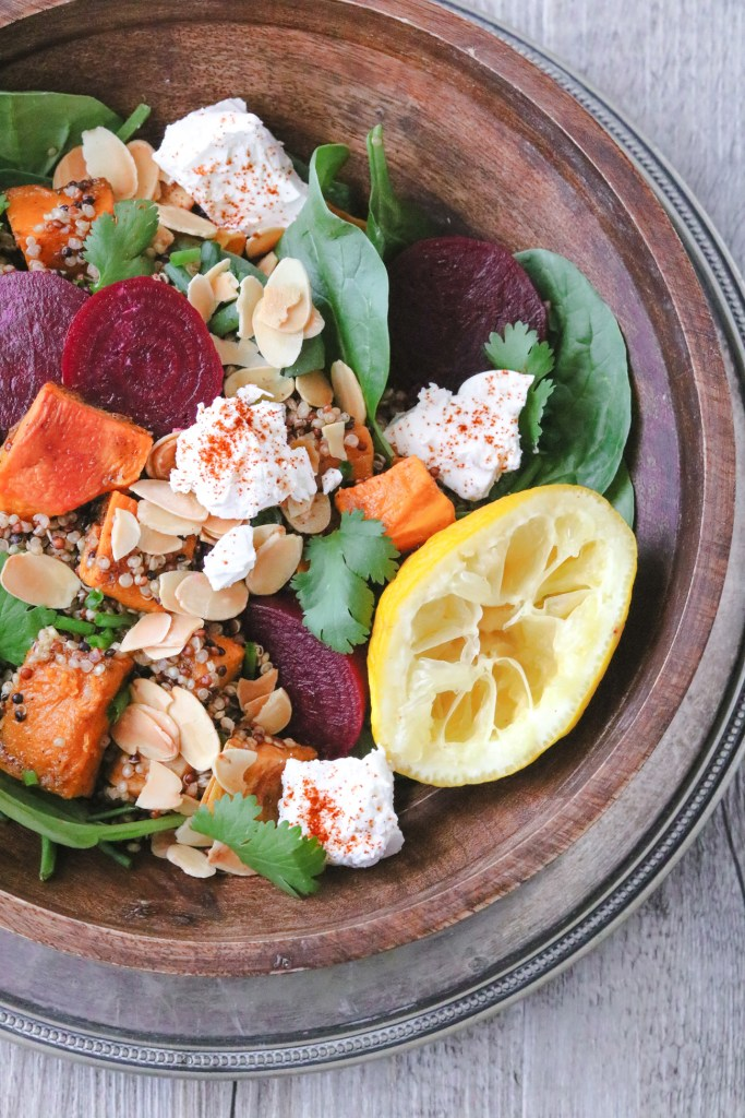 Overhead photo of a wooden bowl filled with roasted pumpkin and sweet potato roasted salad with quinoa, lemon, herbs, roasted almonds, and paprika-sprinkled feta.