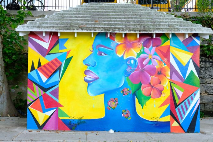 a photo from the post 20 photos to inspire you to visit Bermuda. Street are of a beautiful woman on a local bus stop.