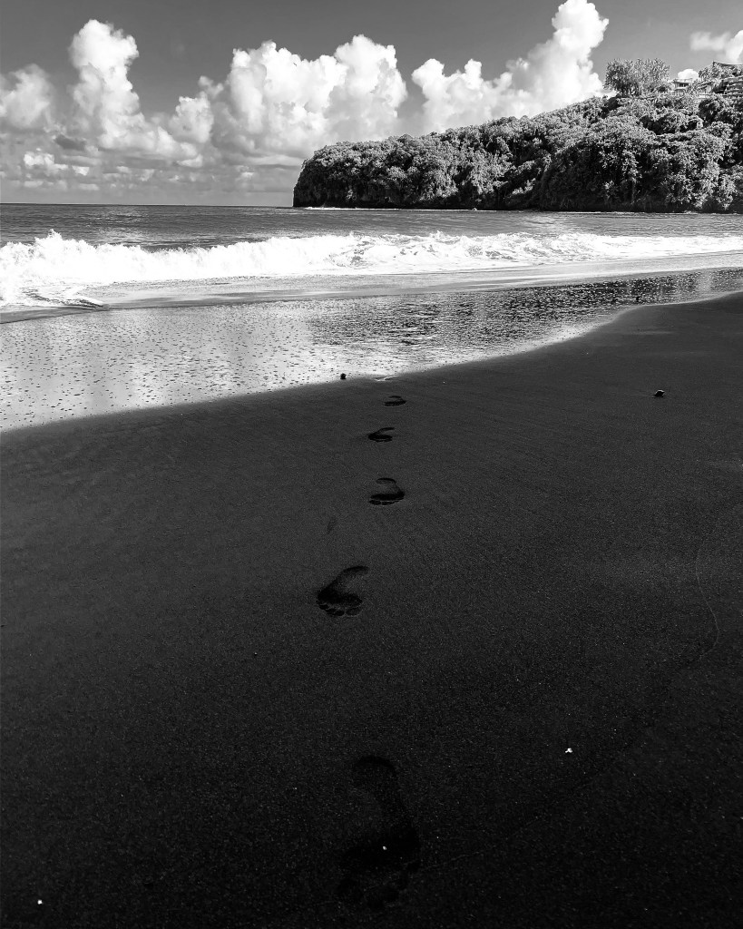 Black and white photo of footsteps on a beach