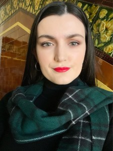 The Ashmosphere - Pale girl with green eyes,  dark hair and red lips smiling wearing a scarf made of Ancient Hunting MacLean tartan