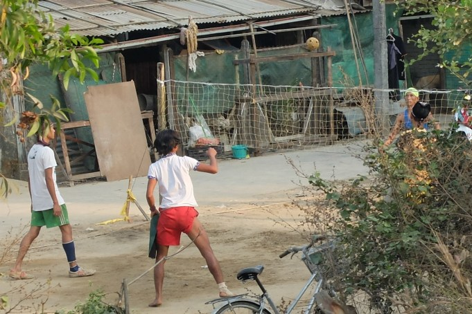 Playing chinlone or caneball. Basically keepy-upie over a net.