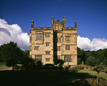 A view of the East Front of Gawthorpe Hall, Lancashire, on a bright sunny day with the garden silhouetted in the foreground
