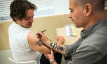 Dinos Chapman takes pen to skin during a for one-day only tattoo parlour in which people could get a distinctively Chapman tattoo. Photograph: Felix Clay/The Guardian