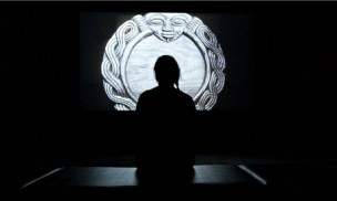 A woman watches a video by Turner prize nominee Duncan Campbell at the awards' exhibition, Tate Britain, London. Photograph: Will Oliver/EPA